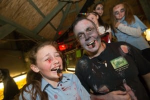 Katelyn Hennessy and her dad James eating scorpions during Halloween Night at the Reptile Village. Photo: Pat Moore.